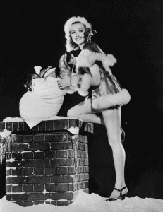 woman santa by chimney with sack of presents